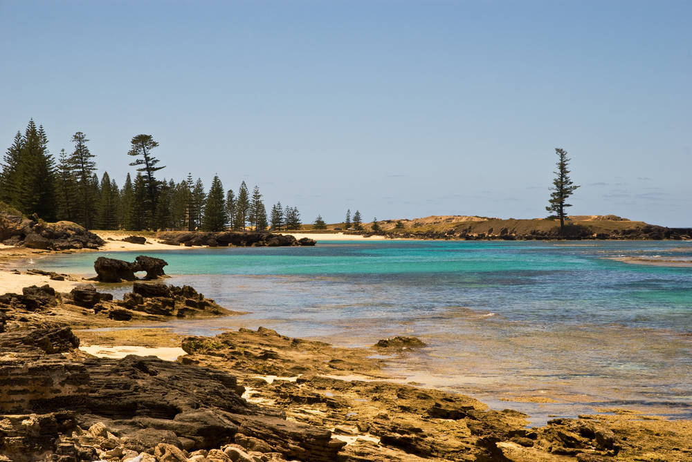 The sparkling crystal waters of Slaughter bay and Emily Bay are lined with Norfolk pines near the old penal settlement of Kingston on Norfolk Island.